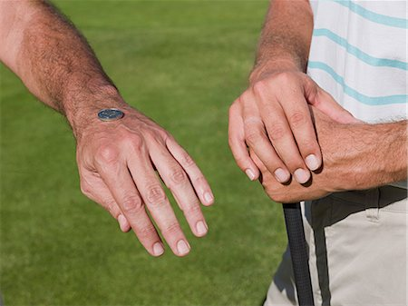 Two mature men playing golf together, tossing a coin Stock Photo - Premium Royalty-Free, Code: 6122-07694522