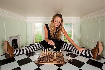 Young woman in small room with chess set Stock Photo - Premium Royalty-Free, Code: 6122-07695443
