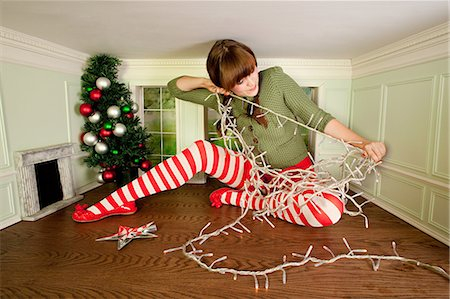 quirky - Young woman in small room with christmas lights Stock Photo - Premium Royalty-Free, Code: 6122-07695442