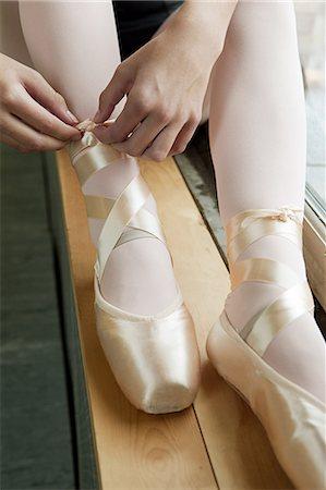 Girl tying ballet shoes Stock Photo - Premium Royalty-Free, Code: 6122-07695437