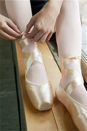 Girl tying ballet shoes Stock Photo - Premium Royalty-Free, Code: 6122-07695437