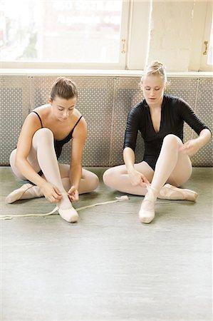 Ballerinas putting on ballet slippers Stock Photo - Premium Royalty-Free, Code: 6122-07695438