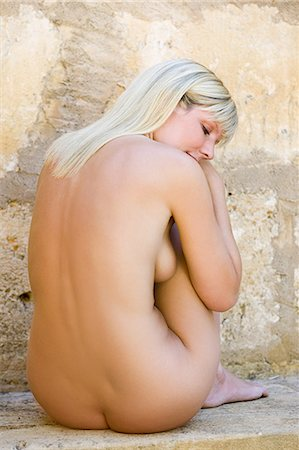 Nude young woman sitting on stone wall Stock Photo - Premium Royalty-Free, Code: 6122-07695560