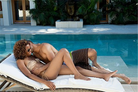Loving couple on lounger by pool Stock Photo - Premium Royalty-Free, Code: 6122-07695607