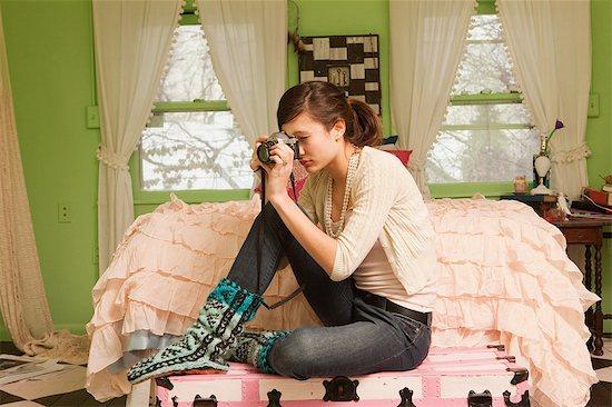Teenage girl sitting on bed taking photograph Stock Photo - Premium Royalty-Free, Image code: 6122-07696576