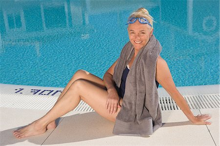 Mature woman sitting by swimming pool Stock Photo - Premium Royalty-Free, Code: 6122-07697052