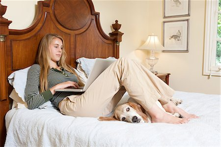 Young woman relaxing on bed with laptop Stock Photo - Premium Royalty-Free, Code: 6122-07697606