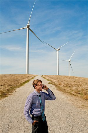 Man using mobile phone in front of wind turbines Stock Photo - Premium Royalty-Free, Code: 6122-07697706