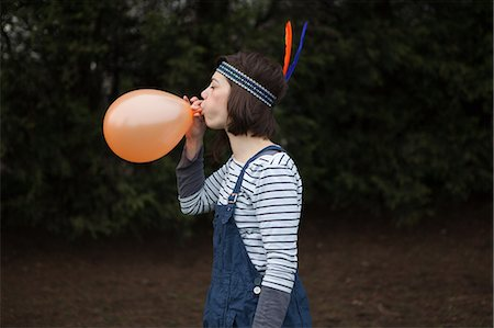 quirky - Young woman in headdress, blowing up a balloon Stock Photo - Premium Royalty-Free, Code: 6122-07697992