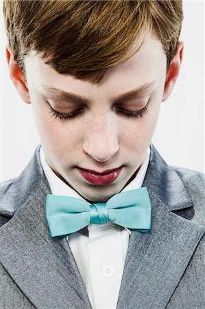 Boy wearing bow tie, looking down Stock Photo - Premium Royalty-Free, Code: 6122-07698238