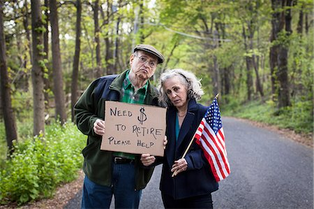 savings - Senior couple holding sign in forest, portrait Stock Photo - Premium Royalty-Free, Code: 6122-07698446