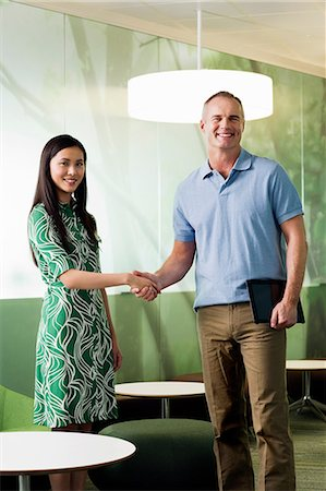 Mature man shaking hands with young woman in meeting Stock Photo - Premium Royalty-Free, Code: 6122-07698421