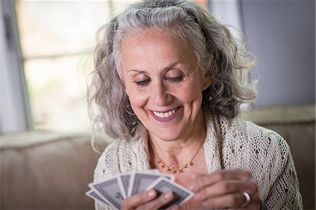 Senior woman playing card game at home Stock Photo - Premium Royalty-Free, Code: 6122-07698436