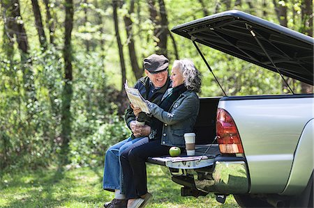 Senior couple reading map while sitting on car trunk in forest Stock Photo - Premium Royalty-Free, Code: 6122-07698438