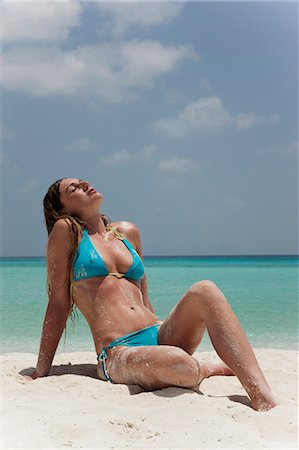Woman sitting in sand on tropical beach Stock Photo - Premium Royalty-Free, Code: 6122-07699136