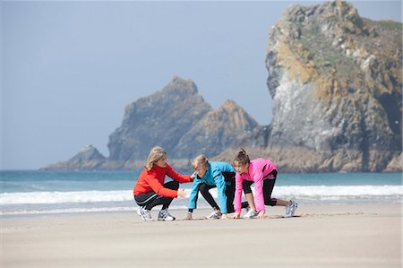 preteen girls stretching - Family running together on beach Stock Photo - Premium Royalty-Free, Code: 6122-07699278
