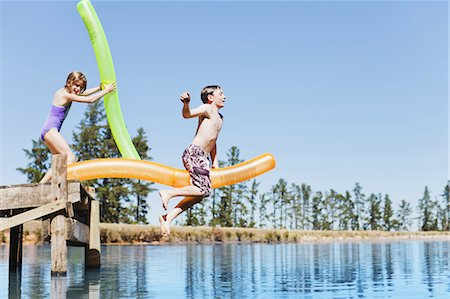 Children jumping into lake from jetty Stock Photo - Premium Royalty-Free, Code: 6122-07699457