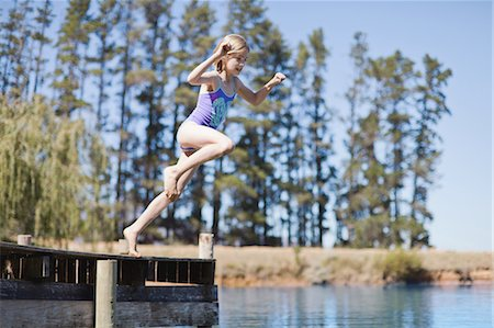 Girl jumping into lake from jetty Stock Photo - Premium Royalty-Free, Code: 6122-07699455