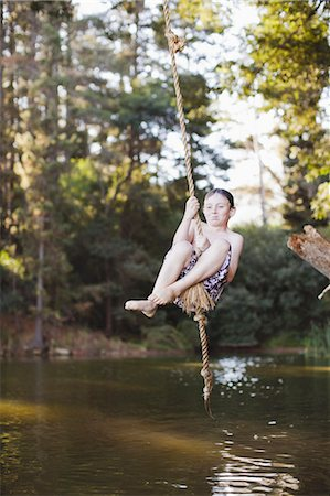 Young girl using rope swing over lake Stock Photo - Premium Royalty-Free, Code: 6122-07699490