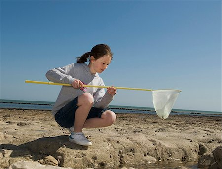 Girl playing with fishing net on beach Stock Photo - Premium Royalty-Free, Code: 6122-07700059