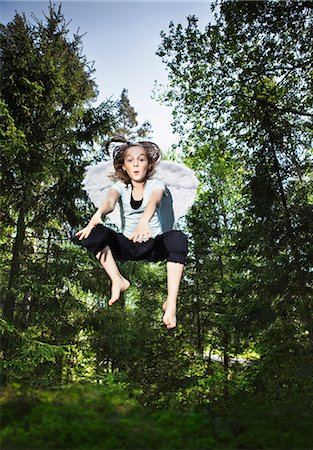 day - Girl wearing wings and jumping in forest Stock Photo - Premium Royalty-Free, Code: 6122-07700188