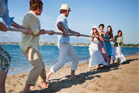 Newlyweds and guests playing tug of war Stock Photo - Premium Royalty-Free, Code: 6122-07700579