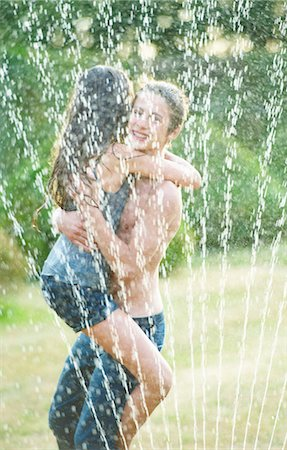 Friends hugging in sprinkler Stock Photo - Premium Royalty-Free, Code: 6122-07702070