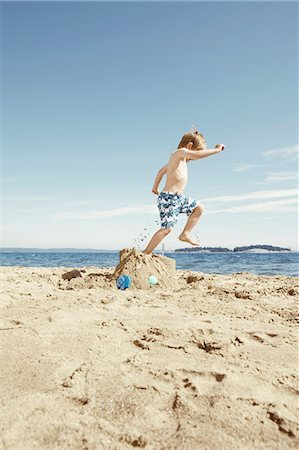 stamped - Boy stomping on sandcastle on beach Stock Photo - Premium Royalty-Free, Code: 6122-07702194
