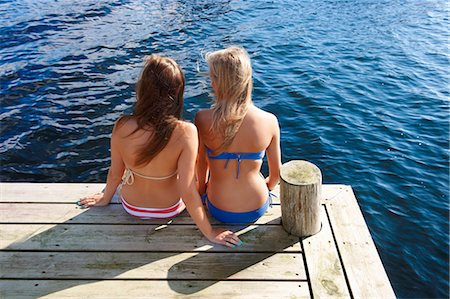 Teenage girls relaxing on wooden pier Stock Photo - Premium Royalty-Free, Code: 6122-07702245