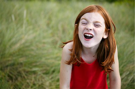 red hair preteen girl - Girl grimacing in tall grass Stock Photo - Premium Royalty-Free, Code: 6122-07702317