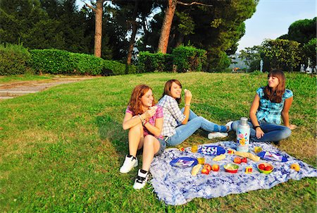 Teenage girls picnicking in rural field Stock Photo - Premium Royalty-Free, Code: 6122-07702576
