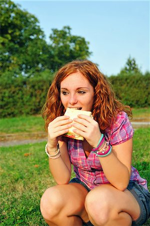 Teenage girl eating sandwich in backyard Stock Photo - Premium Royalty-Free, Code: 6122-07703033