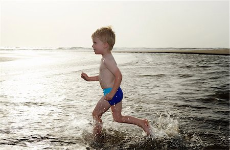 Boy playing in water at beach Stock Photo - Premium Royalty-Free, Code: 6122-07703288