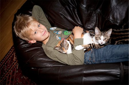 Boy relaxing with cat on couch Stock Photo - Premium Royalty-Free, Code: 6122-07703290