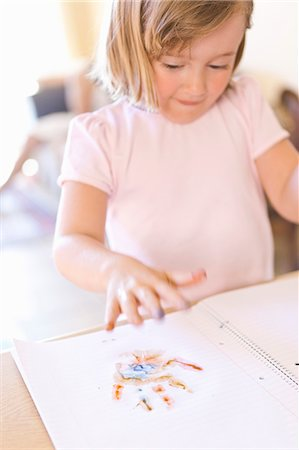 finger painting - Girl finger-painting in notebook Stock Photo - Premium Royalty-Free, Code: 6122-07703434
