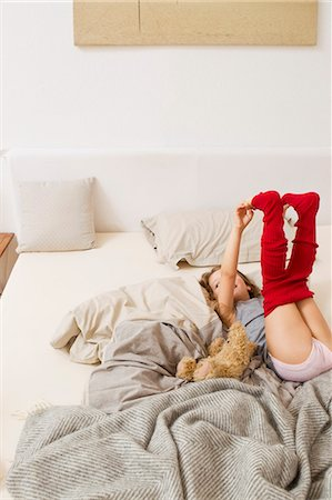 Girl getting dressed on bed Stock Photo - Premium Royalty-Free, Code: 6122-07703518