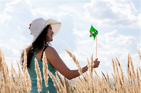 Woman holding pinwheel in wheatfield Stock Photo - Premium Royalty-Free, Code: 6122-07703527