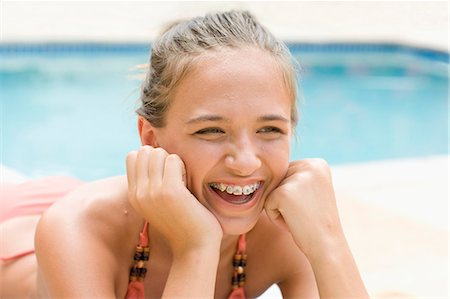 preteen beauty - Teenage girl in braces relaxing by pool Stock Photo - Premium Royalty-Free, Code: 6122-07703983