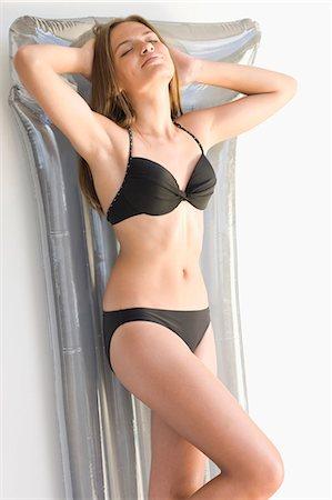 Girl in bikini laying on inflatable raft Stock Photo - Premium Royalty-Free, Code: 6122-07703981