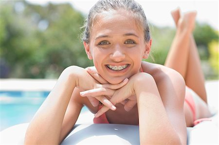 preteen swimsuit - Teenage girl in braces relaxing by pool Stock Photo - Premium Royalty-Free, Code: 6122-07703982