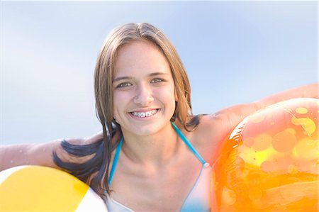 Teenage girl in braces holding toys Stock Photo - Premium Royalty-Free, Code: 6122-07703992