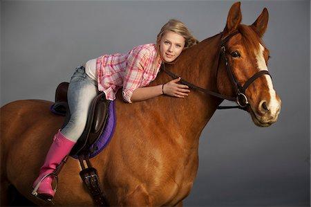 Teenage girl riding horse outdoors Stock Photo - Premium Royalty-Free, Code: 6122-07704338