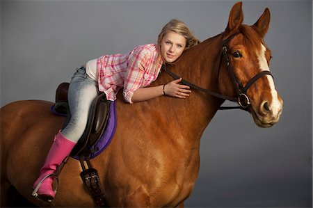 Teenage girl riding horse outdoors Stock Photo - Premium Royalty-Free, Code: 6122-07704338
