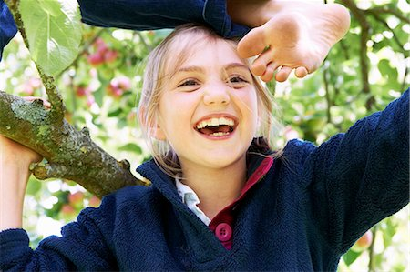 Smiling children climbing tree together Stock Photo - Premium Royalty-Free, Code: 6122-07704848