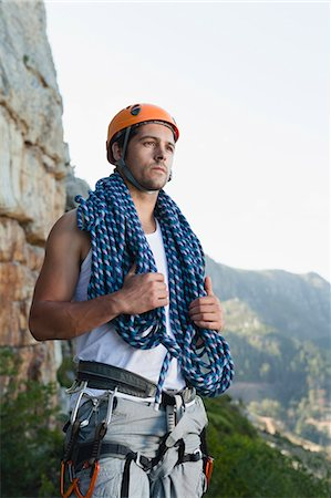 Climber holding coiled rope on mountain Stock Photo - Premium Royalty-Free, Code: 6122-07705000