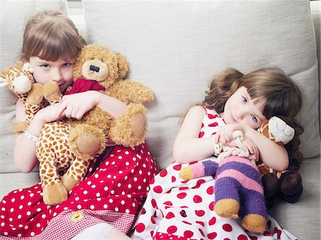 polka dot - Girls holding stuffed animals on sofa Stock Photo - Premium Royalty-Free, Code: 6122-07705328