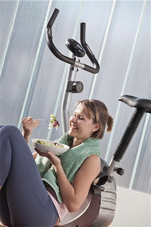 Woman eating salad by exercise machine Stock Photo - Premium Royalty-Free, Code: 6122-07705543