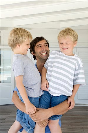 Smiling father holding sons Stock Photo - Premium Royalty-Free, Code: 6122-07705578