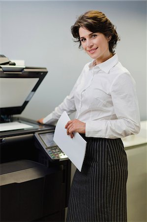 Businesswoman making copies in office Stock Photo - Premium Royalty-Free, Code: 6122-07705738