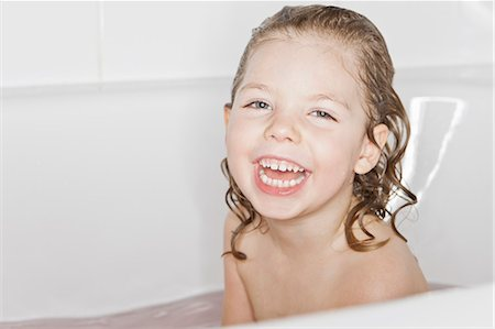 Smiling girl laughing in bath Stock Photo - Premium Royalty-Free, Code: 6122-07705819